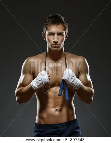 Half-length portrait of half naked sportsman keeping a string with his hands wrapped with elastic bandage, isolated on black