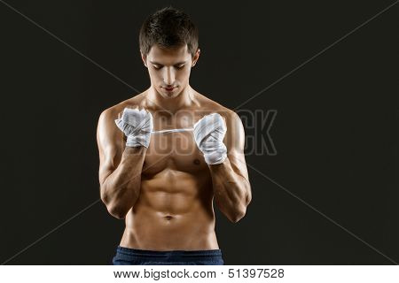 Half-length portrait of hand wrapping nude boxer, isolated on black