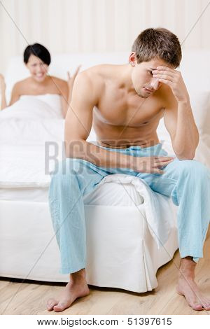 Young couple quarrels in bed. Depressed young man sitting on the edge of the bed. Focus on man