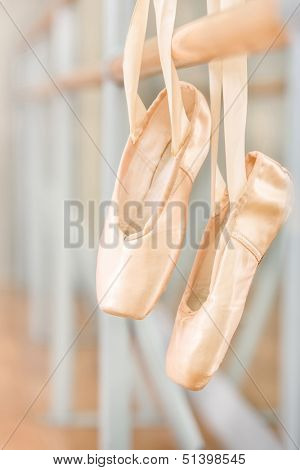 Close up of pointes for ballet on barre near the mirrors in classroom