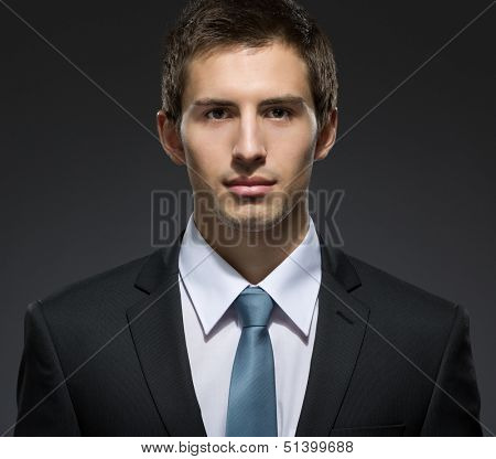 Front view of self-confident business man in dark suit with tie. Concept of professionalism and success in business