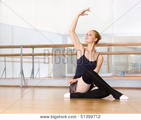 Ballerina works out sitting on the floor in the classroom with barre and mirrors