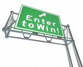 stock photo of raffle prize  - The words Enter to Win on a green freeway road sign to illustrate buying tickets for a lottery or betting in a casino or other place for games - JPG