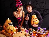 Couple on Halloween party  sitting at trick or treat table.