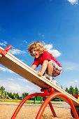 stock photo of seesaw  - Happy little three years old boy child walking over seesaw keeping balance - JPG
