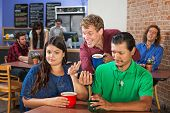 stock photo of pervert  - Annoyed mixed couple with man showing his phone - JPG