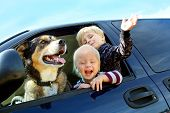 stock photo of baby dog  - Two happy little children and their German Shepherd Dog are waving and peeking their heads out the window of a van - JPG