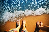 stock photo of wet feet  - Male and female feet are standing on the sandy beach - JPG