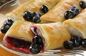 stock photo of crepes  - Closeup of golden blueberry blintzes or crepes with fresh berries - JPG