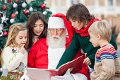 foto of nicholas  - Santa Claus and children reading book against Christmas tree - JPG
