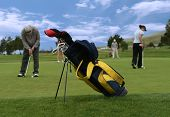 pic of golf bag  - a photo of a golf club bag with golfers in the background  - JPG