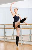 pic of ballet barre  - Wearing leotard and warmers ballerina dances near barre and mirrors in studio - JPG