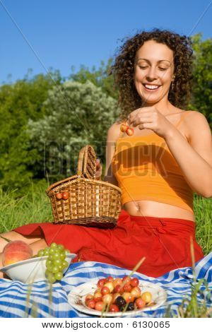 junge Frauen erhalten von Basket Süßkirschen im Garten