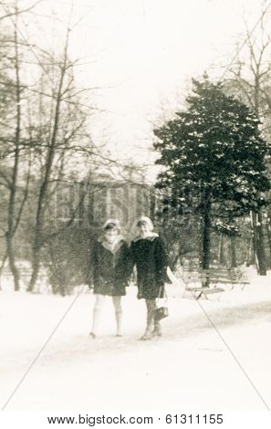 LODZ, POLAND - CIRCA 1960's: Vintage portrait of two girls walking in snowny park