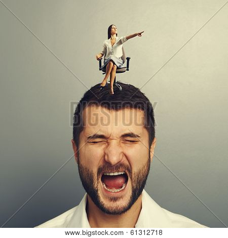 small serious woman sitting on the discontented man and pointing at something over grey background