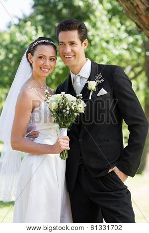 Smiling newly wed couple looking away while standing in park