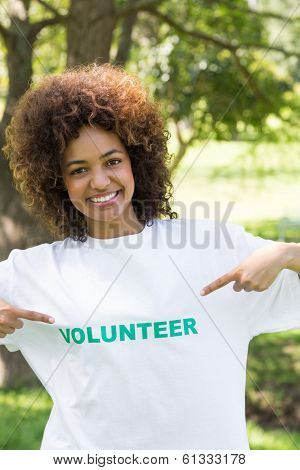 Portrait of confident environmentalist pointing at volunteer tshirt in park