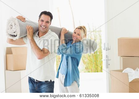 Portrait of a smiling couple carrying rolled rug after moving in a house