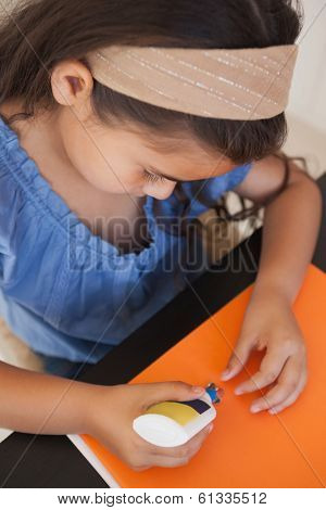 High angle close-up of a young girl doing craftwork at home