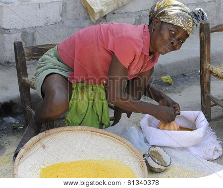 SAINT MARC, HAITI - FEBRUARY 22, 2013.  A woman vendor looking up as she ties a bag of grain she's selling at an outdoor market in Saint Marc, Haiti.