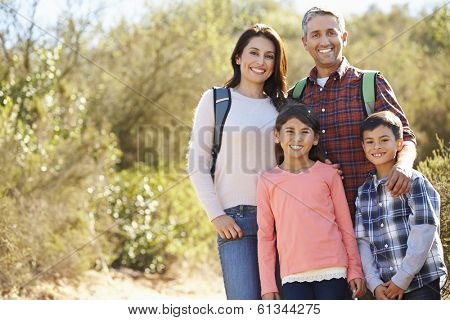 Portrait Of Family Hiking In Countryside Wearing Backpacks