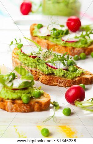 Crostini with pea puree,radish,rocket and cheese