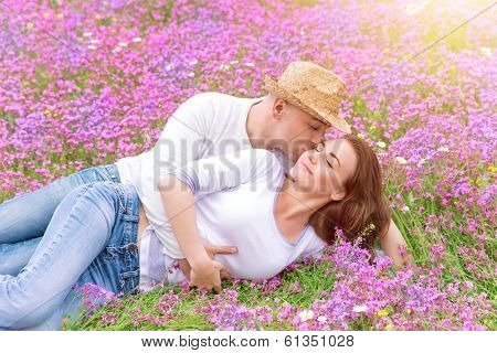 Beautiful cheerful couple lying down on floral glade and kissing, romantic date in spring park, young family, love and romance concept