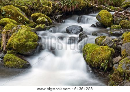 Waterfall flowing between mossy rocks