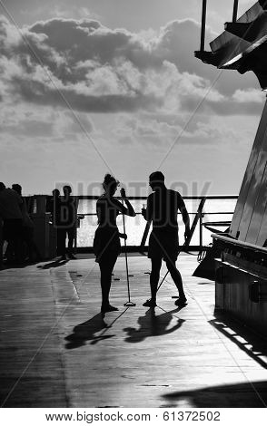 Couple playing Shuffleboard on the deck of a cruise ship