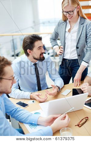 Young businessman explaining his idea to colleagues at meeting in office