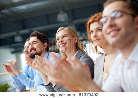 Photo of happy business partners applauding at conference