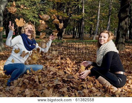 Two Beautiful Young Women Throwing Yellow Leaves
