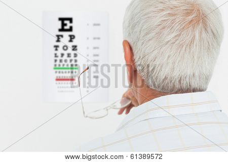 Close-up rear view of a senior man looking at eye chart at medical office