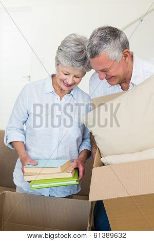 Happy senior couple moving into new home and unpacking boxes