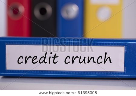The word credit crunch on blue business binder