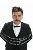 pic of tyranny  - Attractive young man in business suit looks sullen as he stands with chains around him isolated on white - JPG