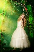 image of loach  - Lovely girl in a lush white dress stands under a floral arch over green background - JPG