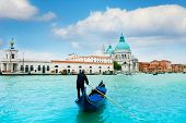 pic of gondolier  - Santa Maria della Salute Basilica in Venice with gondola and gondolier in central Venice Italy - JPG