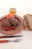 fresh beef meat hamburger on wooden plate with cutlery and rye bread bun on tablecloth with whiskey