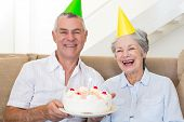 Senior couple sitting on couch celebrating a birthday at home in living room