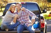 Couple Sitting In Pick Up Truck On Camping Holiday