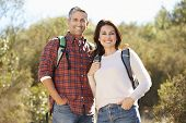 Portrait Of Couple Hiking In Countryside Wearing Backpacks
