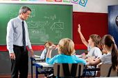 Happy mature professor looking at little schoolboy raising hand in classroom