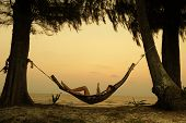 picture of tilt  - Young lady reading the book in the hammock on tropical beach at sunset - JPG