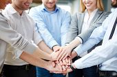 stock photo of collaboration  - Arms of business partners keeping their hands on top of each other symbolizing teamwork - JPG