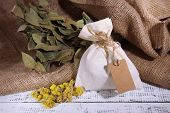 stock photo of sachets  - Textile sachet pouch with dried flowers on wooden table - JPG