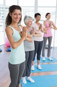 stock photo of namaste  - Happy female trainer with class standing in namaste pose at yoga class - JPG