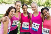 Confident female participants of breast cancer marathon standing together in park