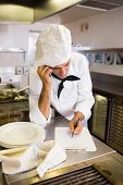 Concentrated male cook writing on clipboard while using cellphone in the kitchen