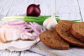 Slices of bread and lard with onion on cutting board on wooden background